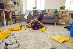 Extremely tired woman lying face down on rug in living-room amid chaos of scattered untidy clothes. Miserable exhausted housewife fallen on floor while cleaning and tidying crazy mess in her house