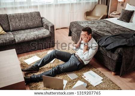 Extremely tired. Young smart successful man feeling extremely tired after working all day in his hotel room #1319207765