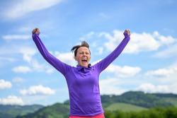Exuberant happy woman celebrating spring during her daily workout jogging in the countryside against blue sky