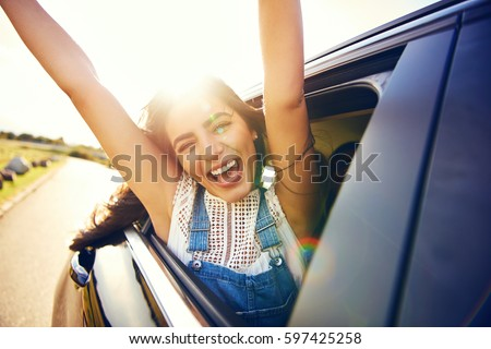 Exuberant young woman celebrating her summer vacation leaning out of an open car window cheering and laughing with outstretched arms