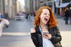 Exuberant young woman cheering at good news on her mobile phone and punching the air with her fist on an urban street with copy space