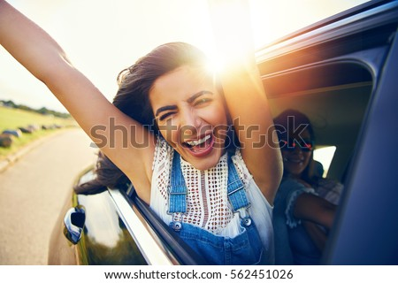 Exuberant young woman cheering with excitement as she leans out of the car window with outstretched arms celebrating the start of her summer vacation with bright sun flare over her shoulder