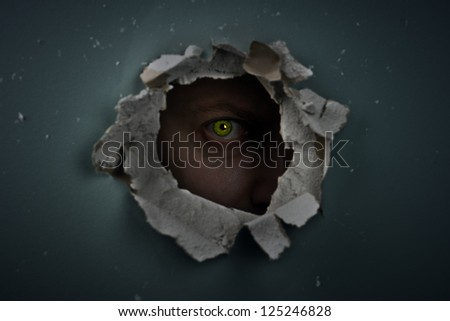 eye behind hole in the wall