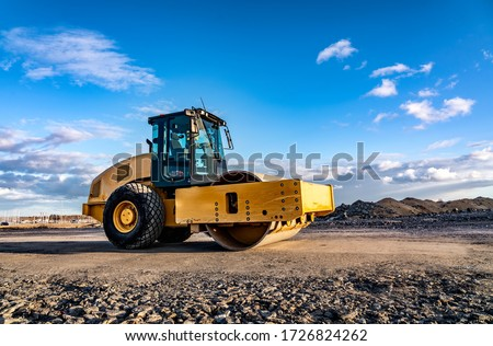 Eye catching yellow road roller with enclosed climate controlled cabin stands on not ready new road, stones, blue sky, clouds, left side view. Clean shiny old heavy tractor Foto stock ©