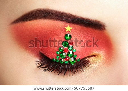 Eye girl makeover christmas tree. Winter christmas makeup. Beauty fashion. Eyelashes. Cosmetic Eyeshadow. Makeup detail. Creative woman holiday make-up