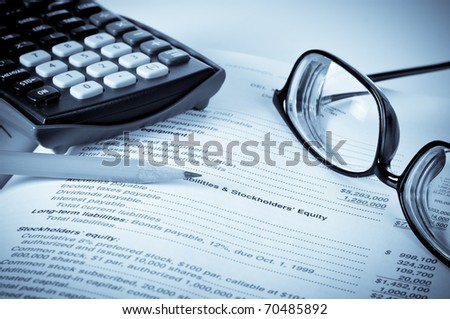 Eye glasses on an accounting book with pencil and calculator with blue tint