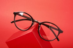 eye glasses on red gift box red background copy space