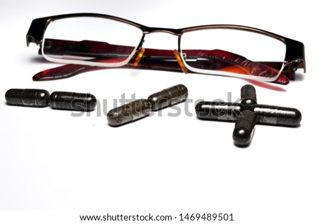 Eye glasses with plus and minus sign made from capsules isolated on white background. Eyesight correction concept #1469489501