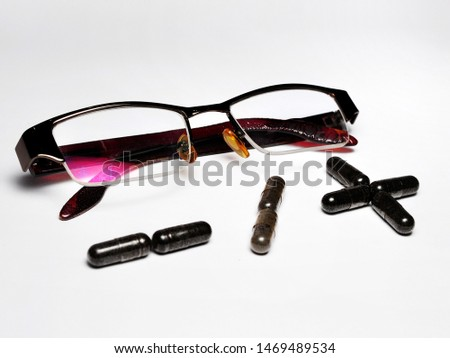 Eye glasses with plus and minus sign made from capsules isolated on white background. Eyesight correction concept #1469489534