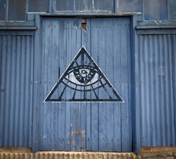 Eye in triangle painted on old warehouse door, all seeing eye conspiracy theory secret society concept