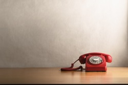 Eye level shot of a retro red telephone (British circa 1960s to 1970s) on a light wood veneer desk or table with off white background providing copy space.