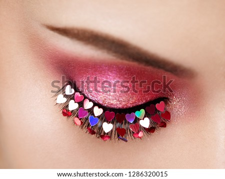 Eye Make-up Girl with a Heart. Valentine's Day Makeup. Beauty Fashion. Eyelashes. Cosmetic Eyeshadow. Makeup Detail. Female Eye with Extreme Long False Eyelashes