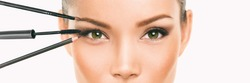 Eye makeup Asian woman professional make up artist applying mascara and eyebrow pencil makeover transformation. Woman putting shadow powder on eyes with makeup brush. Closeup of eyelid and eyebrow.