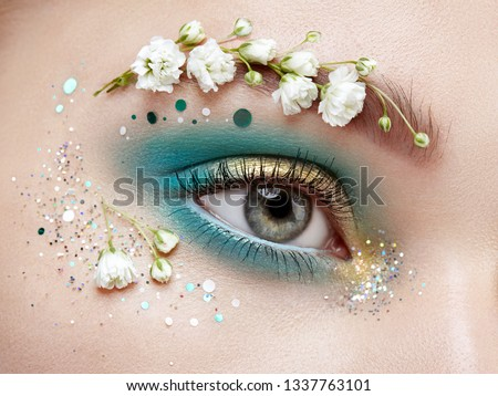 Eye makeup woman with a flowers. Spring makeup. Beauty fashion. Eyelashes. Cosmetic Eyeshadow. Make-up detail. Creative woman floral make-up. White summer flowers