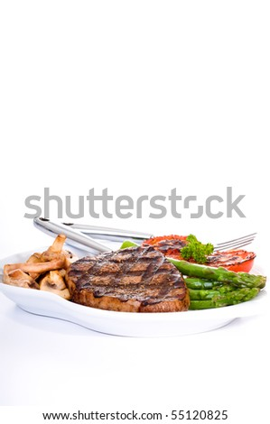 Eye of round steak with grilled vegetables and mushrooms. - stock photo