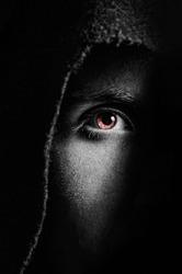 Eye of spooky man in hood