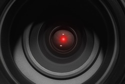 Eye of the camcorder glows red - the concept of video tracking and video monitoring systems. Concept of hidden photo and video shooting, espionage. Camera lens closeup.