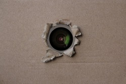 eye of the camcorder looks through a torn hole in an empty brown cardboard, craft paper, concept of secrecy, covert video surveillance, tracking, industrial espionage, blank for designer, copy space