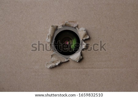 eye of the camcorder looks through a torn hole in an empty brown cardboard, craft paper, concept of secrecy, covert video surveillance, tracking, industrial espionage, blank for designer, copy space Foto stock ©