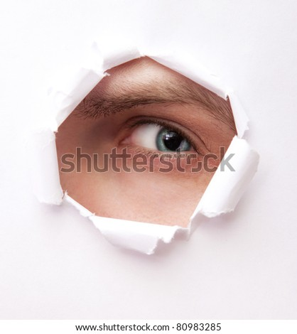Eye of young man looking from paper hole