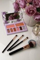 eye shadow palette with brushes and pink bouquet