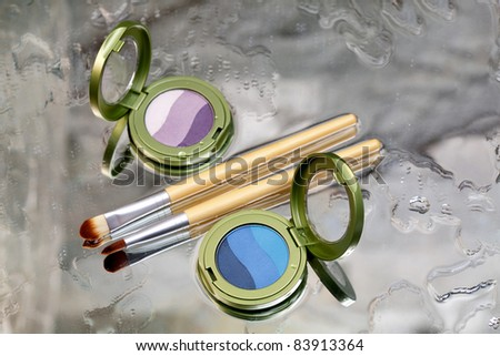 Eye shadows / Blue and purple eye shadow and makeup brush placed on a wet mirror