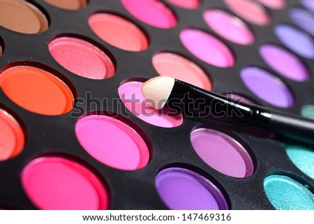 Eye shadows make-up palette and a brush close-up