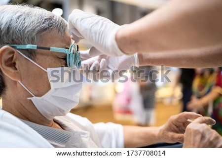 Eye test,Asian senior woman having eyesight test with equipment for check eyes vision,old elderly patient in optometry glasses or trial frame at an optician clinic,eye examination by ophthalmologist
