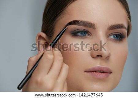 Eyebrow coloring. Woman applying brow tint with makeup brush closeup. Girl model using liquid peel-off brow gel, beauty product on eyebrows ストックフォト ©