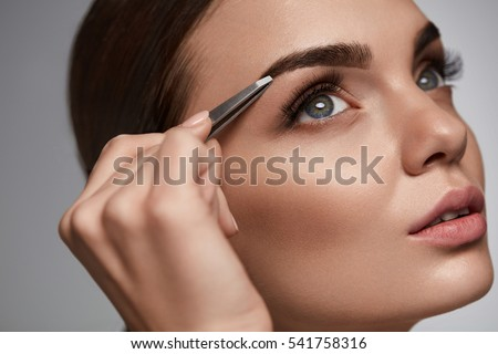 Shutterstock Eyebrow Correction. Closeup Of Beautiful Young Woman With Perfect Makeup And Long Lashes Plucking Eyebrows. Portrait Of Sexy Female Model Face And Tweezers Near Brows. Beauty Concept. High Resolution