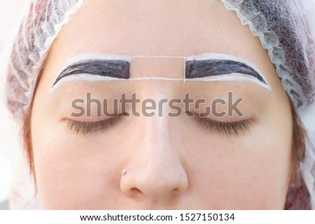 eyebrow dyeing. beauty saloon. the girl lies with her eyes closed on the eyebrow dyeing procedure. The eyebrow master applies brush to the eyebrows of the client.