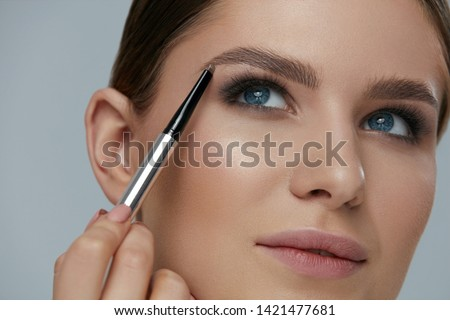 Eyebrow makeup. Beauty model shaping brows with brow pencil closeup. Beautiful sexy woman with professional makeup contouring eyebrows
