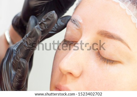 eyebrow shaping in a beauty salon. Shampoo is applied to the girl's eyebrows to remove excess fat and clean hair. before applying eyebrow dye. eyebrow master