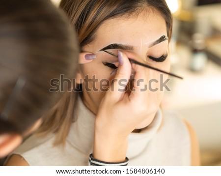 Eyebrow tinting. Close up master applying brow tint with a brush. Cosmetic procedures, eyebrow permanent makeup ストックフォト ©