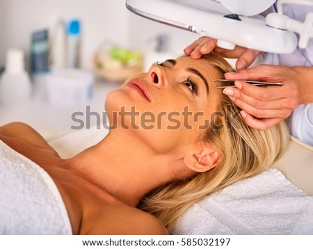 Eyebrow treatment of woman middle-aged in spa salon. Tweezing eyebrow by beautician. 40s old female under cosmetic lamp. European facial procedure. Middle-aged patient looking up.
