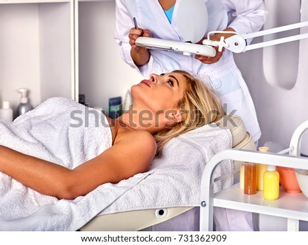 Eyebrow treatment of woman middle-aged in spa salon. Tweezing eyebrow by beautician. 40s old female under cosmetic lamp. European facial procedure. The best spa salon.