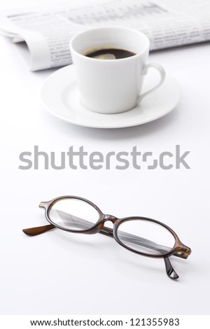 Eyeglasses and coffee, newspaper on white background - stock photo