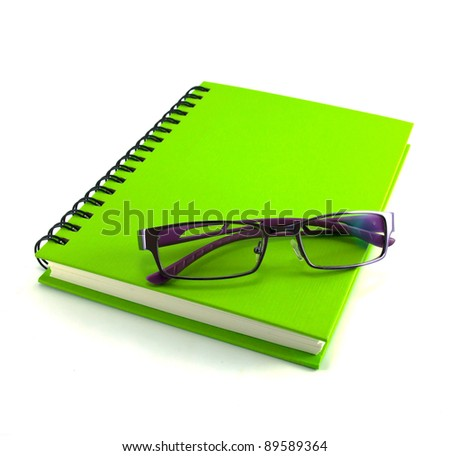 eyeglasses and green notebook isolated on white background, office equipment