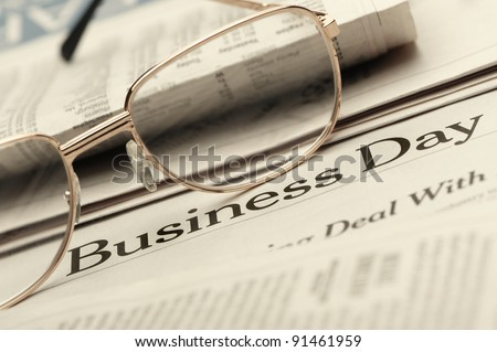 Eyeglasses lie on the newspaper with title Business day. A photo close up. Selective focus