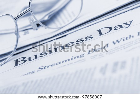 Eyeglasses lie on the newspaper with title Business day.Blue toned. A photo close up. Selective focus