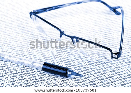 Eyeglasses on binary system page - stock photo