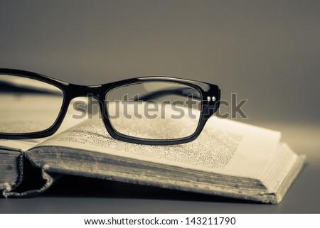 Eyeglasses on opened old book
