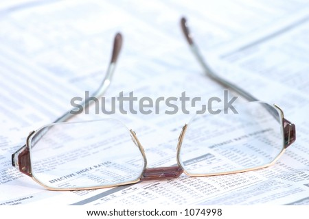 Eyeglasses on top of a financial newspaper. - stock photo