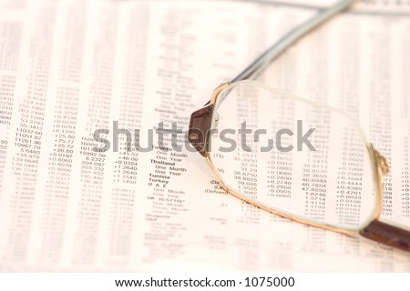 Eyeglasses on top of a financial newspaper with currency exchange rates