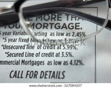 Eyeglasses over mortgage rates ad in a newspaper