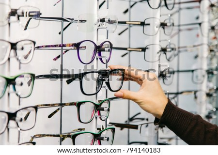 Eyeglasses shop. Stand with glasses in the store of optics. Woman's hand chooses glasses. #794140183