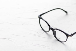Eyeglasses with black frame on white background. Eye glasses.  Round glasses with transparent lenses. Close up eyeglasses with blurry technique. Fashion accessory. Ophthalmology theme.