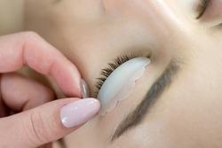 Eyelash Care Treatment: eyelash lifting, staining, curling, laminating and extension for lashes.  Close up of beauty model's face with perfect fresh skin and long eyelashes, lash lift laminate.