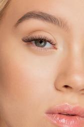 Eyelash extension procedure. Beautiful female eyes with long lashes closeup.