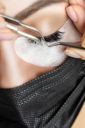 Eyelash Extension Procedure. Beautiful Woman with Extreme Long False Eyelashes. Makeup, Cosmetics. Beauty, Skincare. Woman in medical mask.
